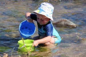 RW besig om sy emmertjie vol water te skep in die heerlike koel rivier water.